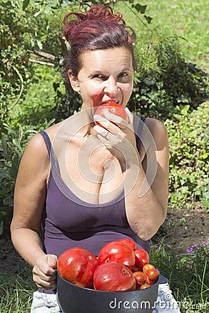 Smiling woman eating organic tomato