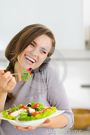 Smiling woman eating salad and talking mobile phone
