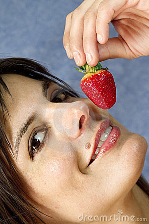 Smiling woman  eating strawberry fruit