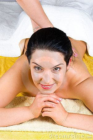 Smiling woman enjoying a back massage at spa