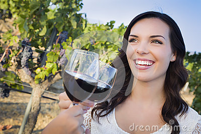 Smiling Woman Enjoying Glass of Wine in Vineyard With Friends