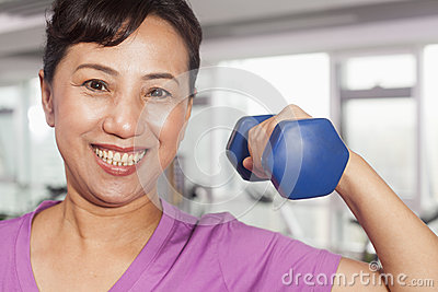 Smiling woman exercising with weights, arm raised, in the gym
