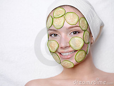 Smiling woman with facial mask of cucumber