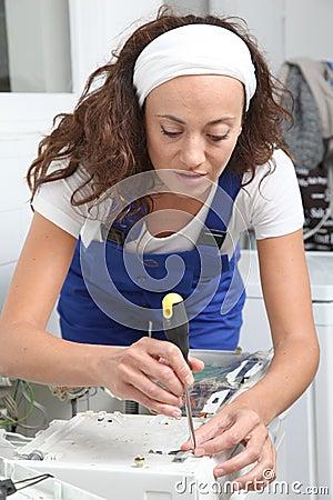 Smiling woman fixing washing machine