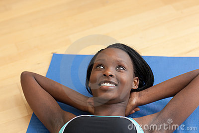 Smiling woman in gym clothes doing sit-ups