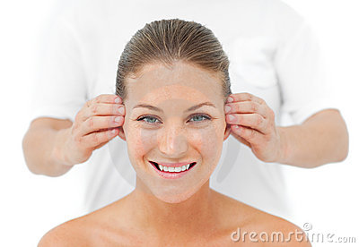 Smiling woman having a head massage in a spa