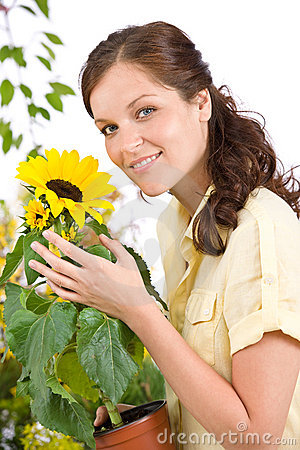 Smiling woman holding flower pot with sunflower