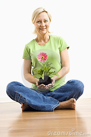Smiling woman holding gerber daisy.