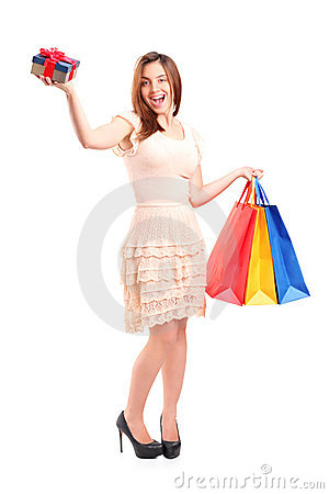 Smiling woman holding a shopping bags and a gift