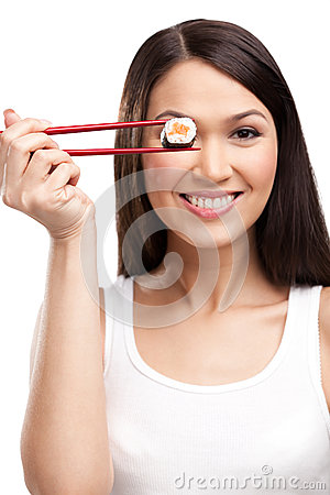 Smiling woman holding sushi roll with a chopsticks