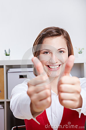 Smiling woman holding two thumbs up