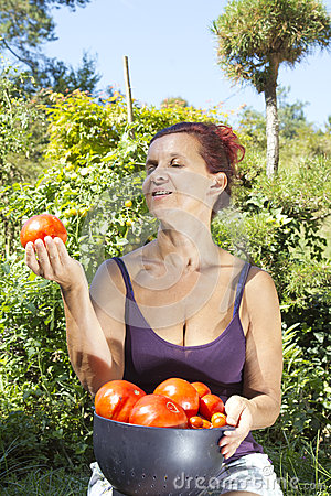 Smiling woman holds organic tomato