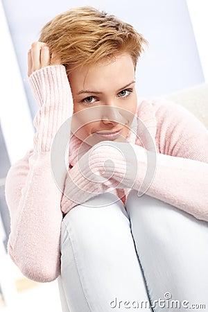 Smiling woman hugging knees