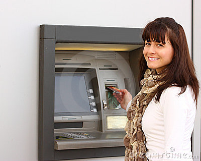 Smiling woman insert a card in an ATM