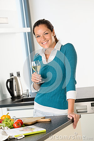 Smiling woman kitchen drinking wine preparing vegetables