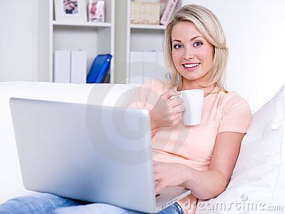 Smiling woman with laptop and cup of coffee