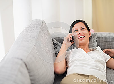Smiling woman laying on sofa and speaking mobile
