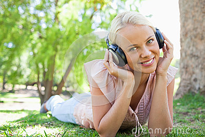 Smiling woman listening to music while lying