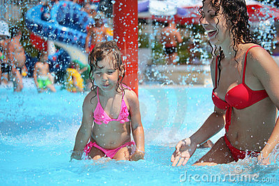 Smiling woman and little girl bathes in pool