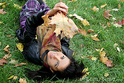 Smiling woman lying on a carpet of leaves