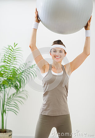 Smiling woman making exercise with fitness ball