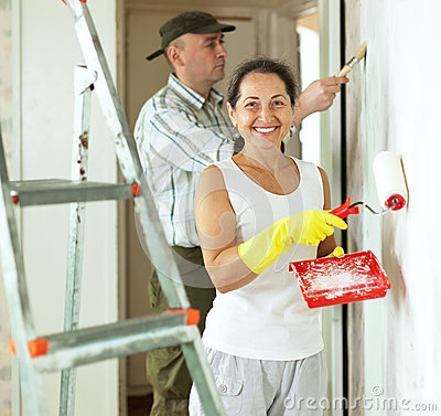 Smiling woman and man makes repairs