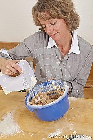 Smiling woman mixing dough