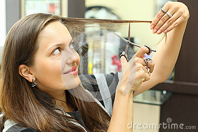Smiling woman mows her hair with scissors