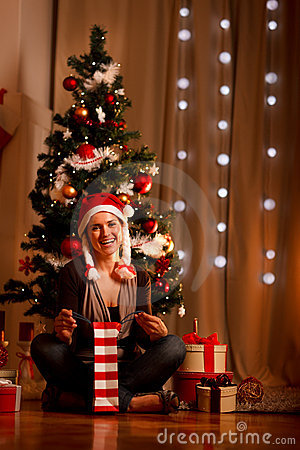 Smiling woman near Christmas tree opening present