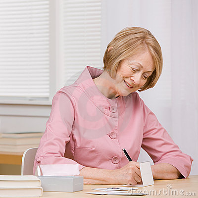 Smiling woman paying bills with checks at desk
