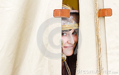 Smiling woman peeping behind tent