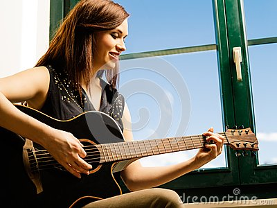 Smiling woman playing guitar by a window