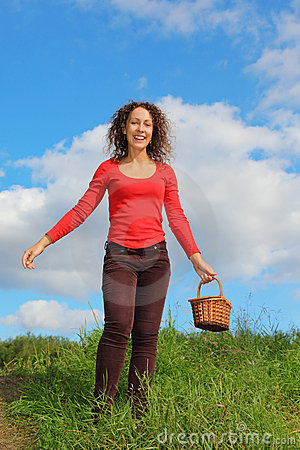 Smiling woman with pottle is walking outdoors
