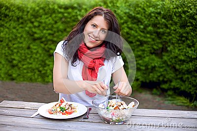 Smiling Woman Preparing a Bowl of Salad