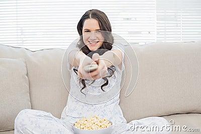 Smiling woman in pyjamas having popcorn while watching tv