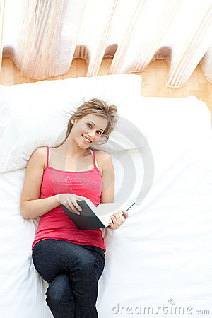 Smiling woman reading a book lying on her bed
