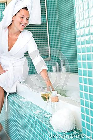 Smiling woman relaxing wrapped towel bathroom bathtub