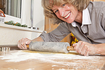 Smiling woman rolling dough