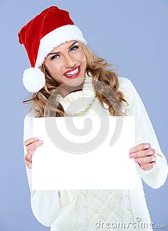 Smiling woman in Santa hat holding blank board