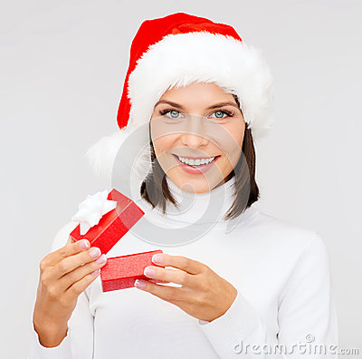 Smiling woman in santa hat with small gift box