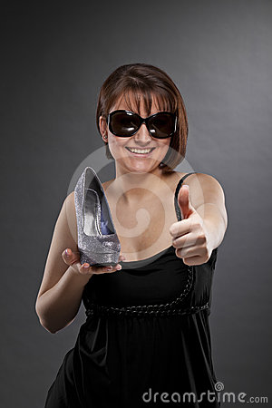 Smiling woman with shoe posing thumbs up