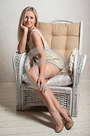 Smiling woman in short dress is posing on a chair