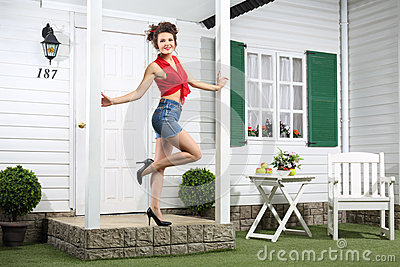 Smiling woman in shorts poses next to simple entrance door