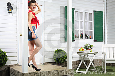 Smiling woman in shorts stands next to white entrance door