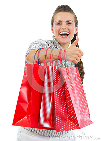 Smiling woman showing thumbs up with shopping bags