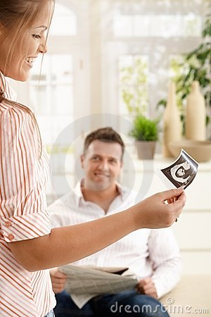 Smiling woman showing ultrasound picture to man