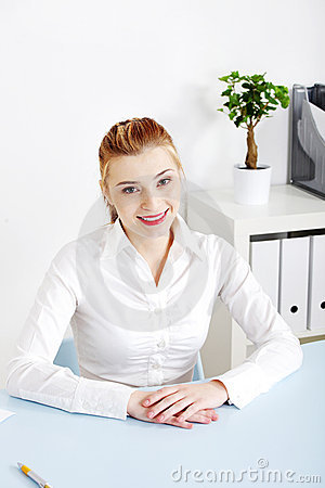 Smiling woman sitting behind the desk