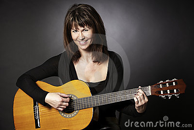 Smiling woman sitting with guitar.