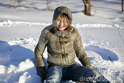 Smiling woman sitting on snow