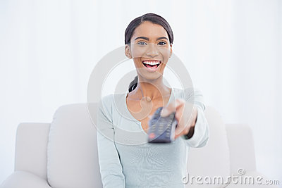 Smiling woman sitting on sofa changing tv channel